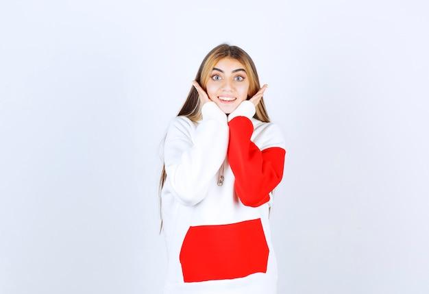 Porträt einer schönen frau im warmen hoodie, die unter dem kinn steht und händchen hält