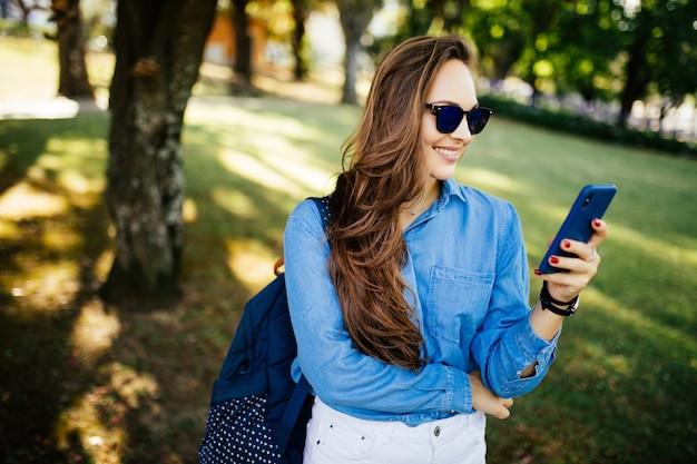 Porträt einer schönen frau in der sonnenbrille, die auf dem smartphone in einem park mit einem grünen unscharfen hintergrund tippt