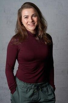 Porträt einer schönen frau in einem roten rollkragenpullover nahe einer weißen backsteinmauer.
