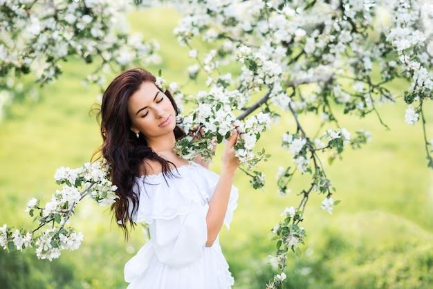 Porträt einer schönen frau in einem weißen kleid in einem frühlingsgarten. ein mädchen mit geschlossenen augen atmet den duft blühender bäume ein.