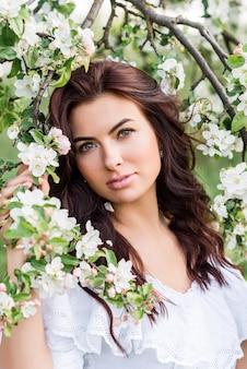 Porträt einer schönen frau in einem weißen kleid in einem frühlingsgarten. ein mädchen zwischen den blühenden bäumen.