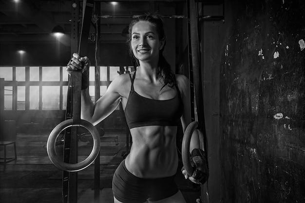 Porträt einer schönen frau in einer sportuniform in der nähe der gymnastikringe. fitness, bodybuilding, gymnastikkonzept. gemischte medien