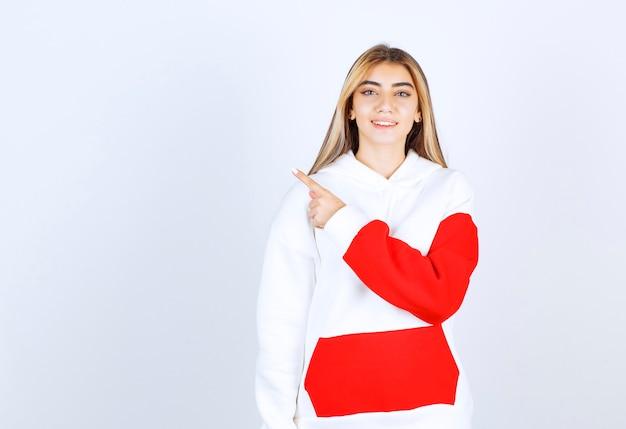 Porträt einer schönen frau in warmem hoodie, die steht und wegzeigt