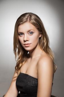 Porträt einer schönen frau mit blonden, gewellten haaren, die in die kamera schaut. studioaufnahme