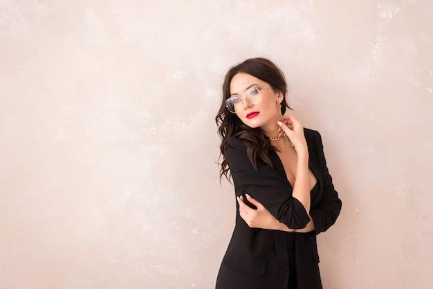 Porträt einer schönen frau mit brille auf beigem hintergrund. ein mädchen in einem schwarzen anzug und einer brille. platz für text