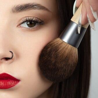 Porträt einer schönen frau mit einem make-up-pinsel, beschnittene ansicht.