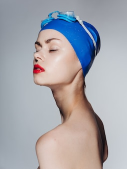 Porträt einer schönen frau mit geschlossenen augen in einer blauen badekappen-nahaufnahme
