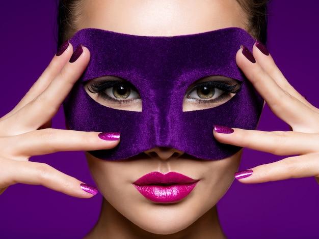 Porträt einer schönen frau mit lila nägeln und violetter theatermaske im gesicht.