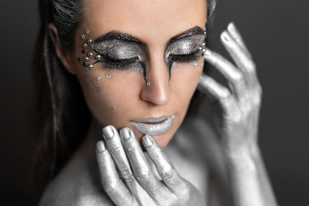 Porträt einer schönen frau mit silberner farbe auf haut und haaren.