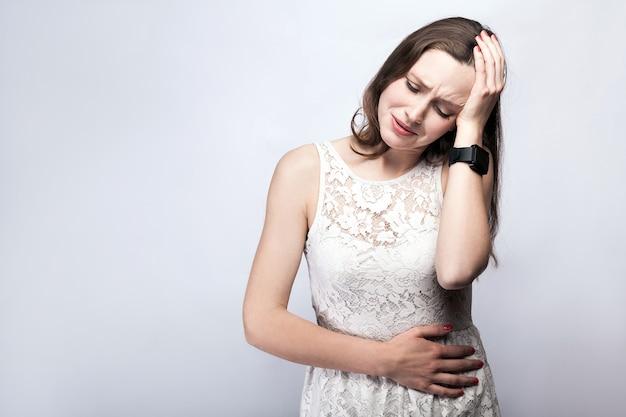 Porträt einer schönen frau mit sommersprossen und weißem kleid und intelligenter uhr mit magenschmerzen auf silbergrauem hintergrund. gesundheits- und medizinkonzept.