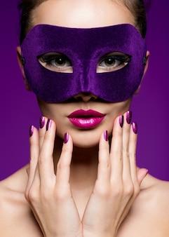 Porträt einer schönen frau mit violetten nägeln und theatermaske im gesicht.