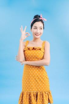 Porträt einer schönen frau pinup retro-stil zeigt auf sie lächelnd lachend isolierte blaue wand. körpersprache, gestik, psychologie.