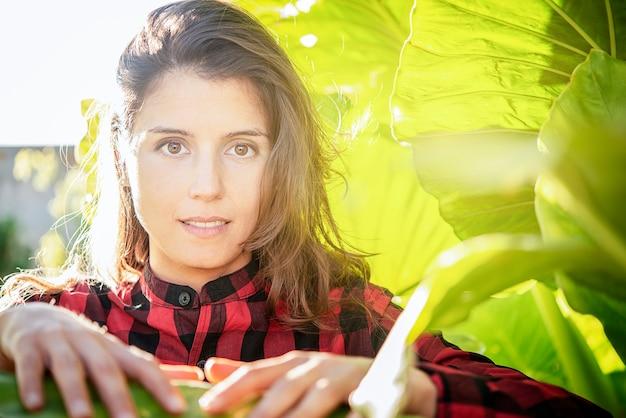Porträt einer schönen frau unter dem pflanzenkonzept des ökologischen friedens und der freiheit