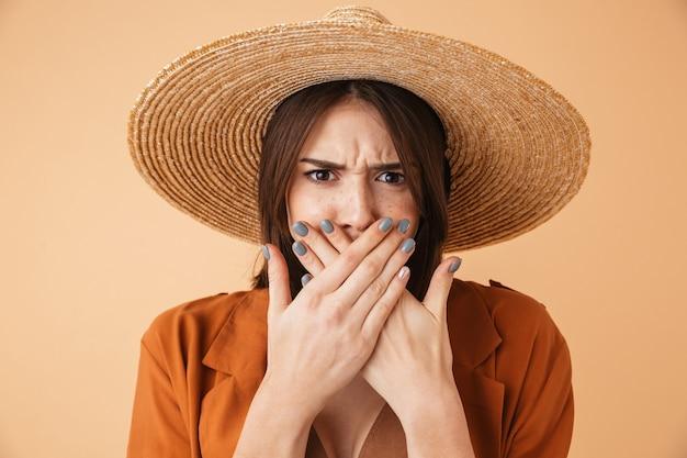 Porträt einer schönen frustrierten jungen frau mit strohhut, die isoliert über beige wand steht, mund bedecken