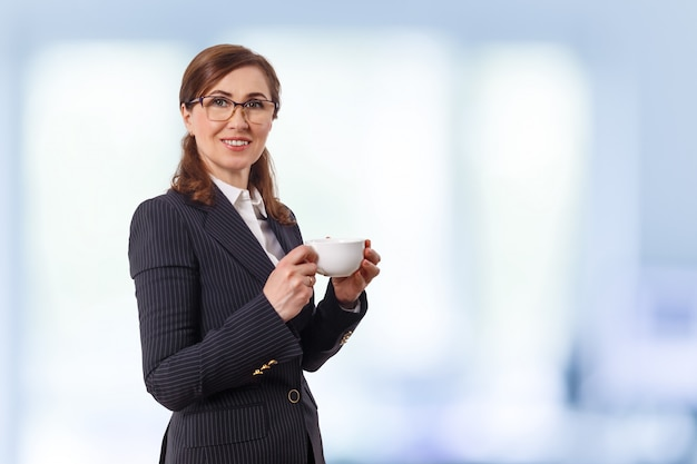 Porträt einer schönen geschäftsfrau 50 ohren alt mit tasse kaffee im büro.