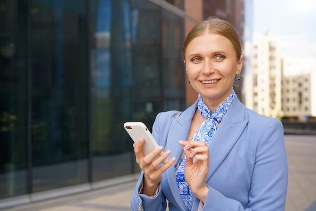 Porträt einer schönen geschäftsfrau in einer blauen jacke, die am telefon vor dem hintergrund eines bürogebäudes spricht