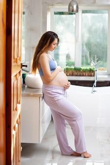 Porträt einer schönen glücklichen schwangeren brünette in einem hellen badezimmer. morgen sonnenschein. lächeln, glück. vertikal. foto in hoher qualität