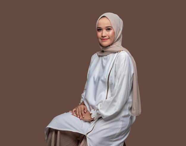 Porträt einer schönen hijab-frau saß auf einem stuhl, der auf einfarbigem hintergrund isoliert war.