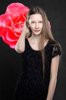 Porträt einer schönen jugendlichen wird vor dem hintergrund einer roten rose geschossen. schlanke mädchenblondine mit blauen augen.