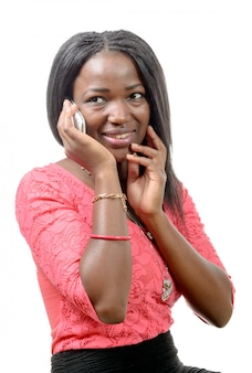 Porträt einer schönen jungen afrikanischen frau, die am handy gegen weiß spricht