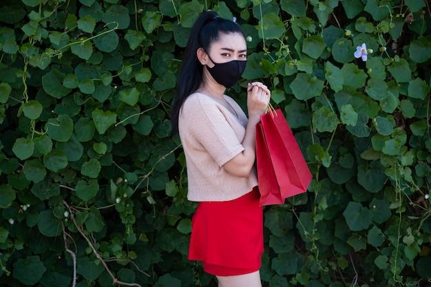 Porträt einer schönen jungen asiatischen frau, die eine gesichtsmaske mit dem halten von einkaufstüten an der blattwand trägt, tragen frauen rosa kleidung und roten rock, der die kamera betrachtet
