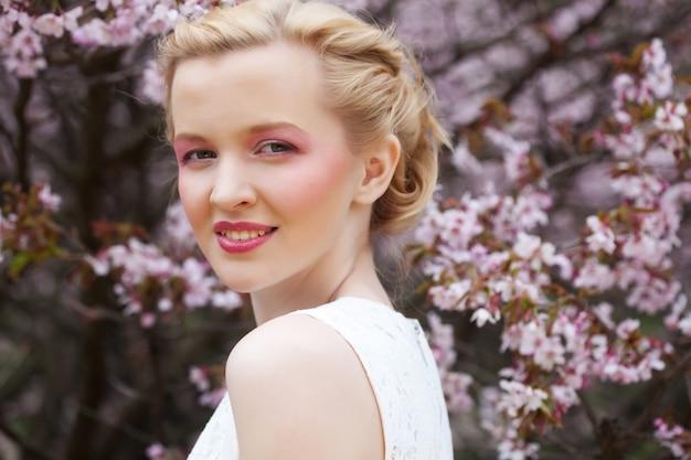 Porträt einer schönen jungen blonden frau auf einem hintergrund der rosa kirschblüten im frühjahr