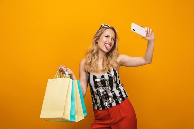 Porträt einer schönen jungen blonden frau, die lokal über gelbem hintergrund steht und ein selfie nimmt
