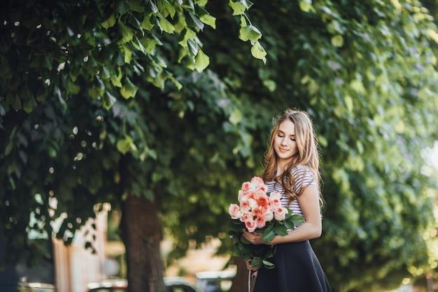 Porträt einer schönen jungen blonden frau, die mit einem strauß rosen steht