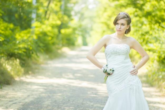 Porträt einer schönen jungen braut in der natur. junge frau, die einen kleinen blumenstrauß von weißen rosen in ihren händen hält