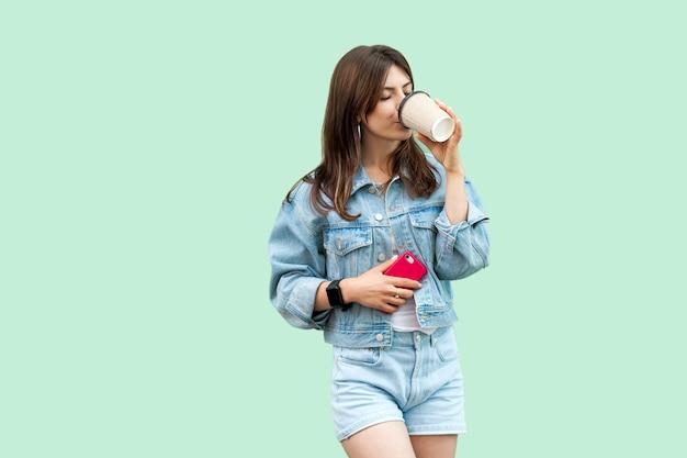 Porträt einer schönen jungen brünetten frau im lässigen denim-stil, die einwegbecher steht und hält, trinkt und sich ausruht und genießt. indoor-studioaufnahme, auf grünem hintergrund isoliert.