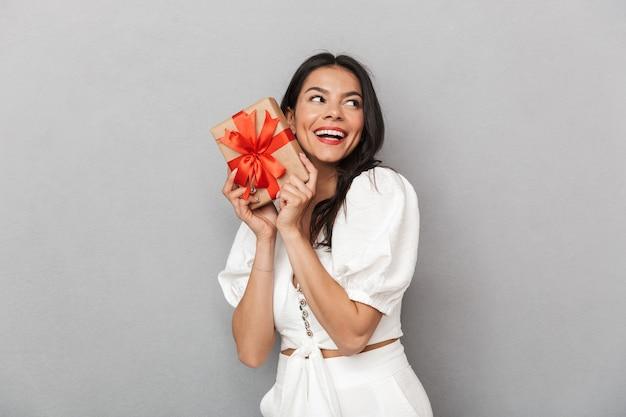 Porträt einer schönen jungen brünetten frau mit sommeroutfit, die isoliert über grauer wand steht und geschenkbox zeigt