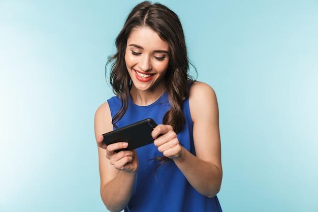 Porträt einer schönen jungen brünettenfrau, die über blau steht und apps auf handy spielt