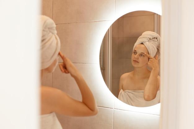 Porträt einer schönen jungen erwachsenen frau mit einem handtuch auf dem kopf, die im badezimmer steht und ihr gesicht im spiegel untersucht und ihre augenbraue berührt.