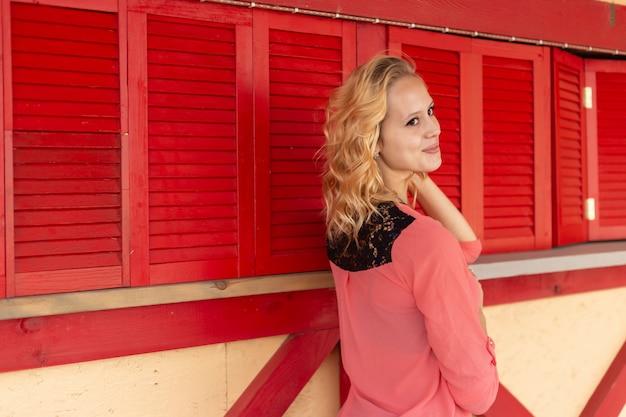 Porträt einer schönen jungen frau auf dem hintergrund einer roten hölzernen wand
