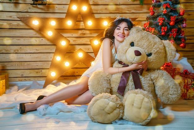 Porträt einer schönen jungen frau auf dem hintergrund eines weihnachtsbaums