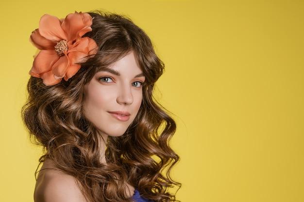 Porträt einer schönen jungen frau auf einem gelben mit einer blume im haar