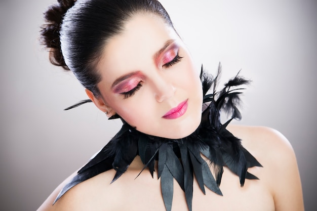 Porträt einer schönen jungen frau auf einer grauen wand, professionellem make-up und frisur