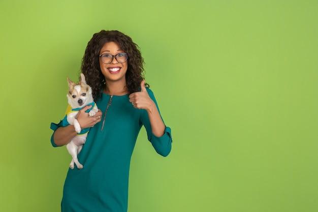 Porträt einer schönen jungen frau des afroamerikaners mit kleinem hündchen auf grün