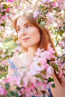 Porträt einer schönen jungen frau des rothaarigen frühlingsmädchens in den rosa blumen, die das freie konzept des apfelgartenallergiens genießen