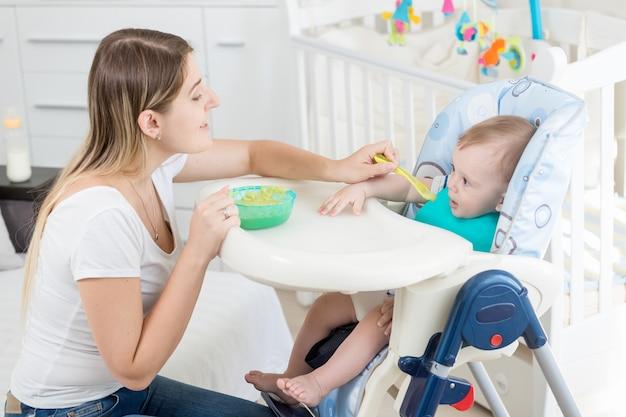 Porträt einer schönen jungen frau, die 9 monate altes baby füttert, das im hochstuhl sitzt sitting