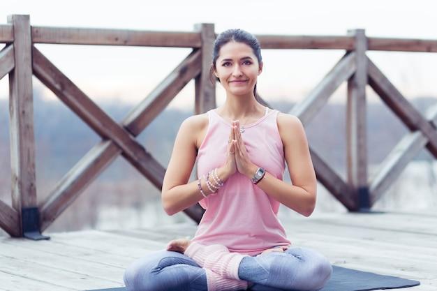 Porträt einer schönen jungen frau, die an der natur arbeitet und yoga- und pilates-übungen macht