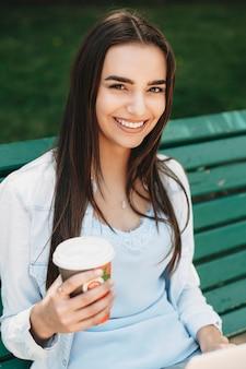 Porträt einer schönen jungen frau, die auf einer bank mit einer tasse kaffee in einer hand sitzt und kamera betrachtet, die draußen in der stadt lacht.