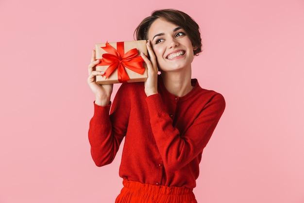 Porträt einer schönen jungen frau, die das rote kleid trägt, das lokal steht und geschenkbox hält