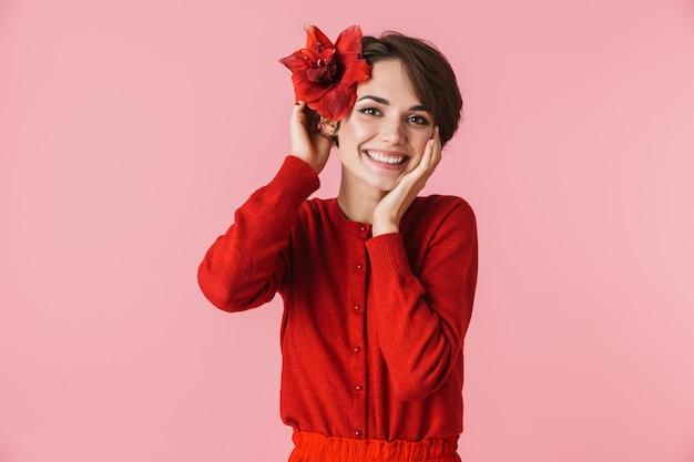 Porträt einer schönen jungen frau, die das rote kleid trägt, das lokal steht und mit einer blume aufwirft