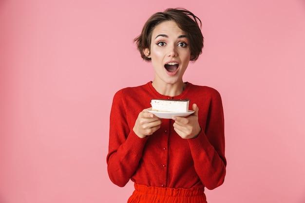 Porträt einer schönen jungen frau, die das rote kleid trägt, das lokal über rosa hintergrund steht und ein stück kuchen auf einem teller hält