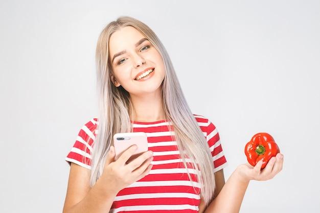 Porträt einer schönen jungen frau, die ein gemüse und telefon auf einem weißen hintergrund hält.