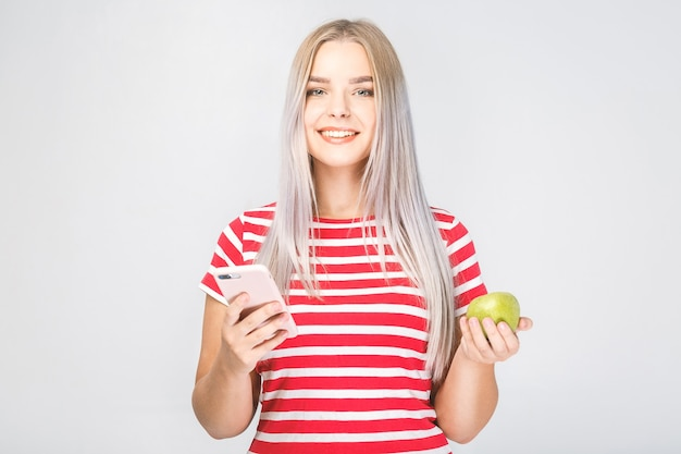 Porträt einer schönen jungen frau, die einen apfel und ein telefon auf einem weißen hintergrund hält.
