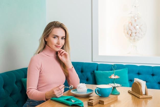 Porträt einer schönen jungen frau, die im café betrachtet kamera sitzt
