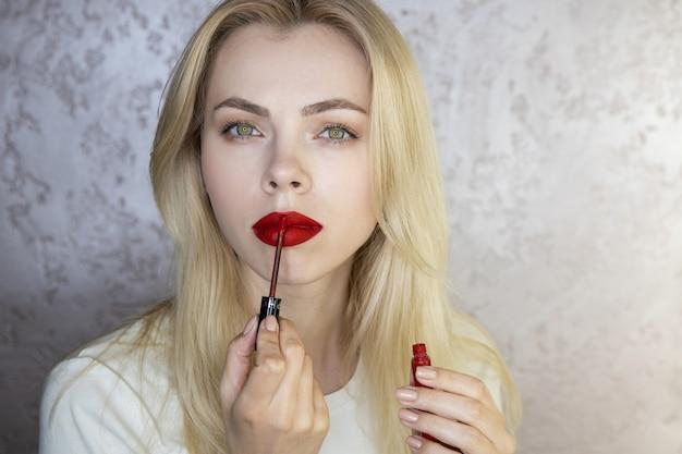 Porträt einer schönen jungen frau, die make-up mit leuchtend roten lippen tut