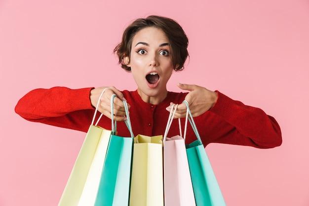 Porträt einer schönen jungen frau, die rote kleidung trägt, die isoliert steht und einkaufstaschen trägt